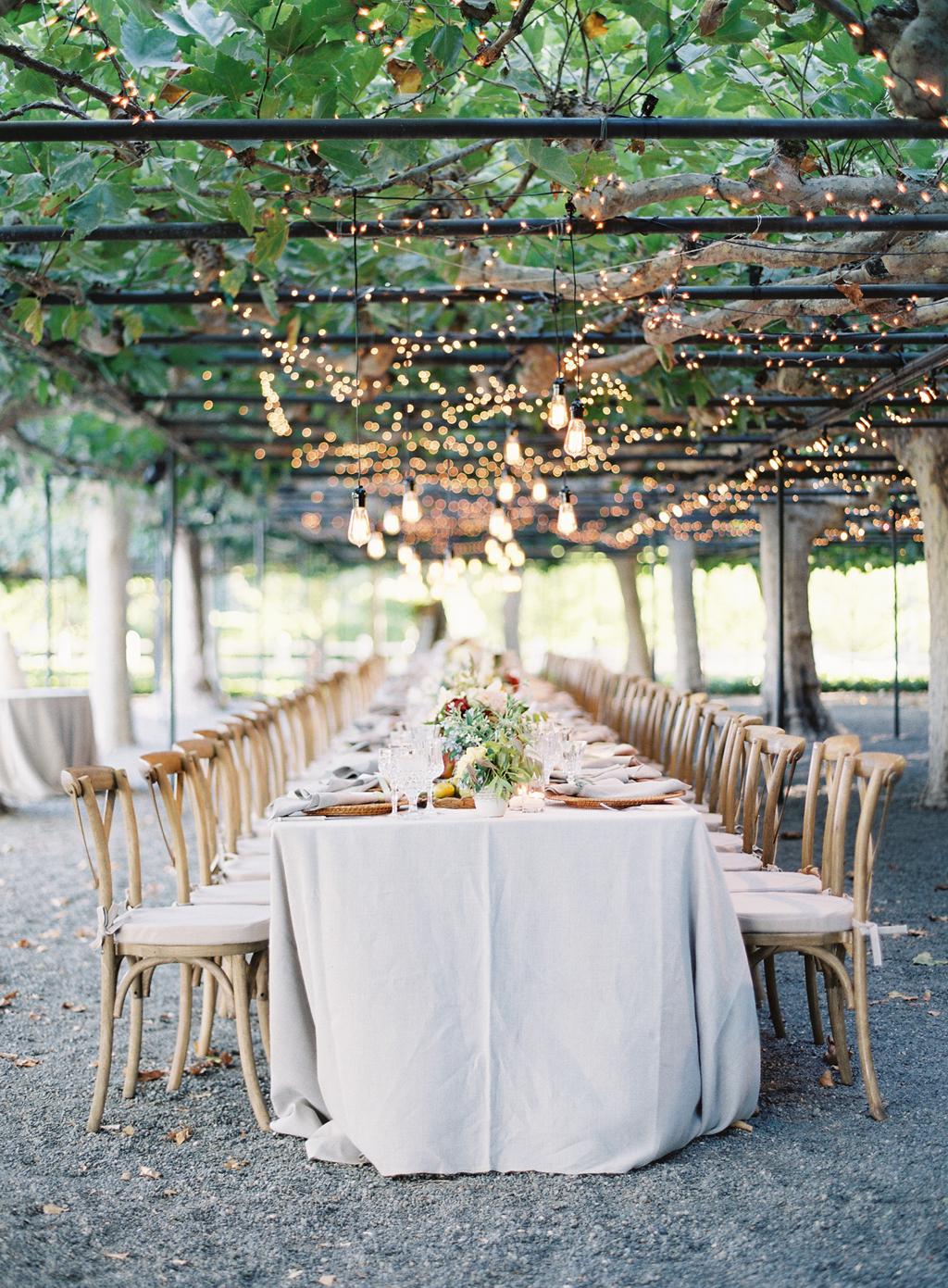 cafe lights hang over the long tables in the reception area at beaulieu gardens in napa valley