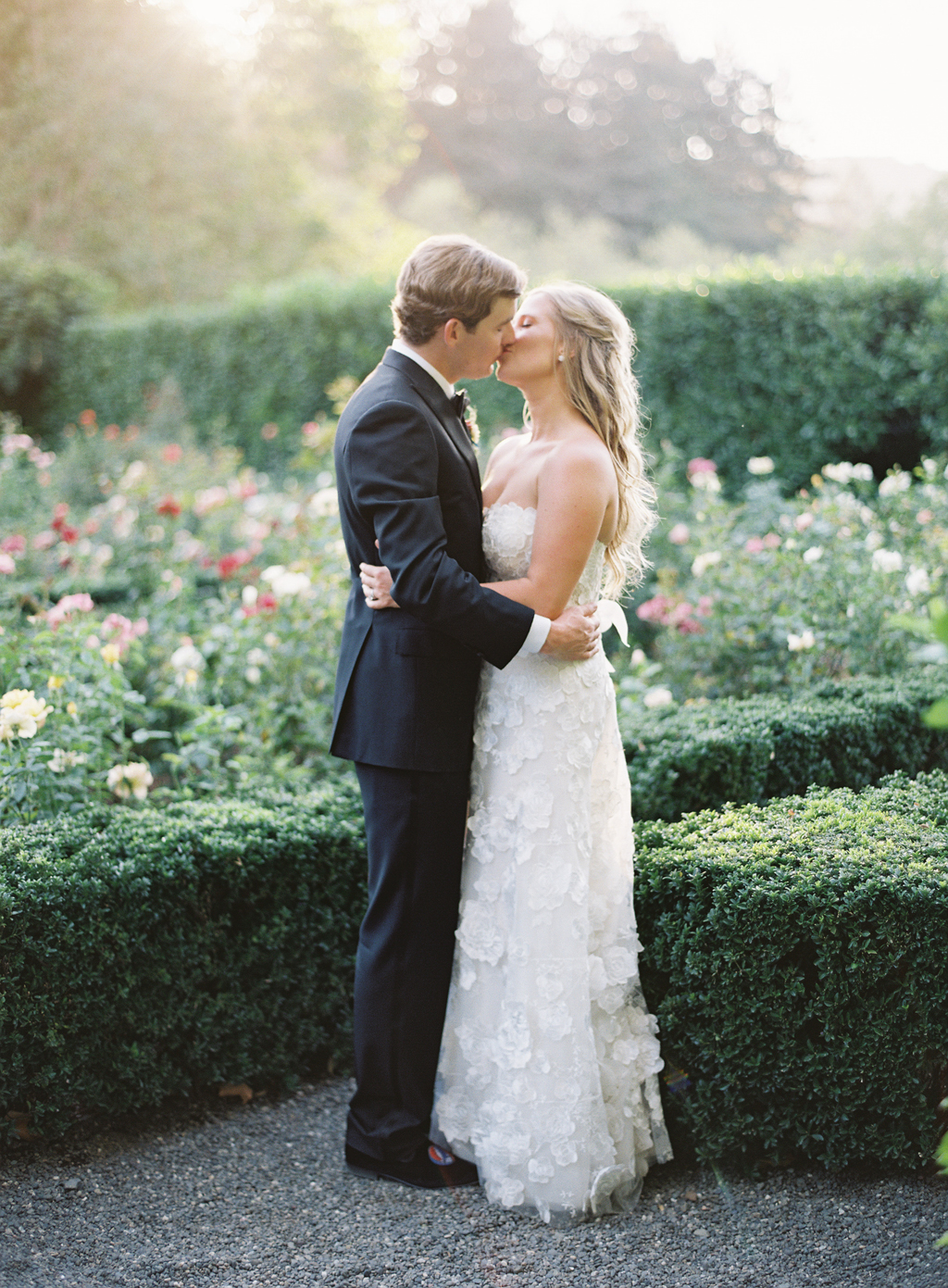 a couple poses for a kiss in the rose garden at beaulieu gardens on their wedding day film photography