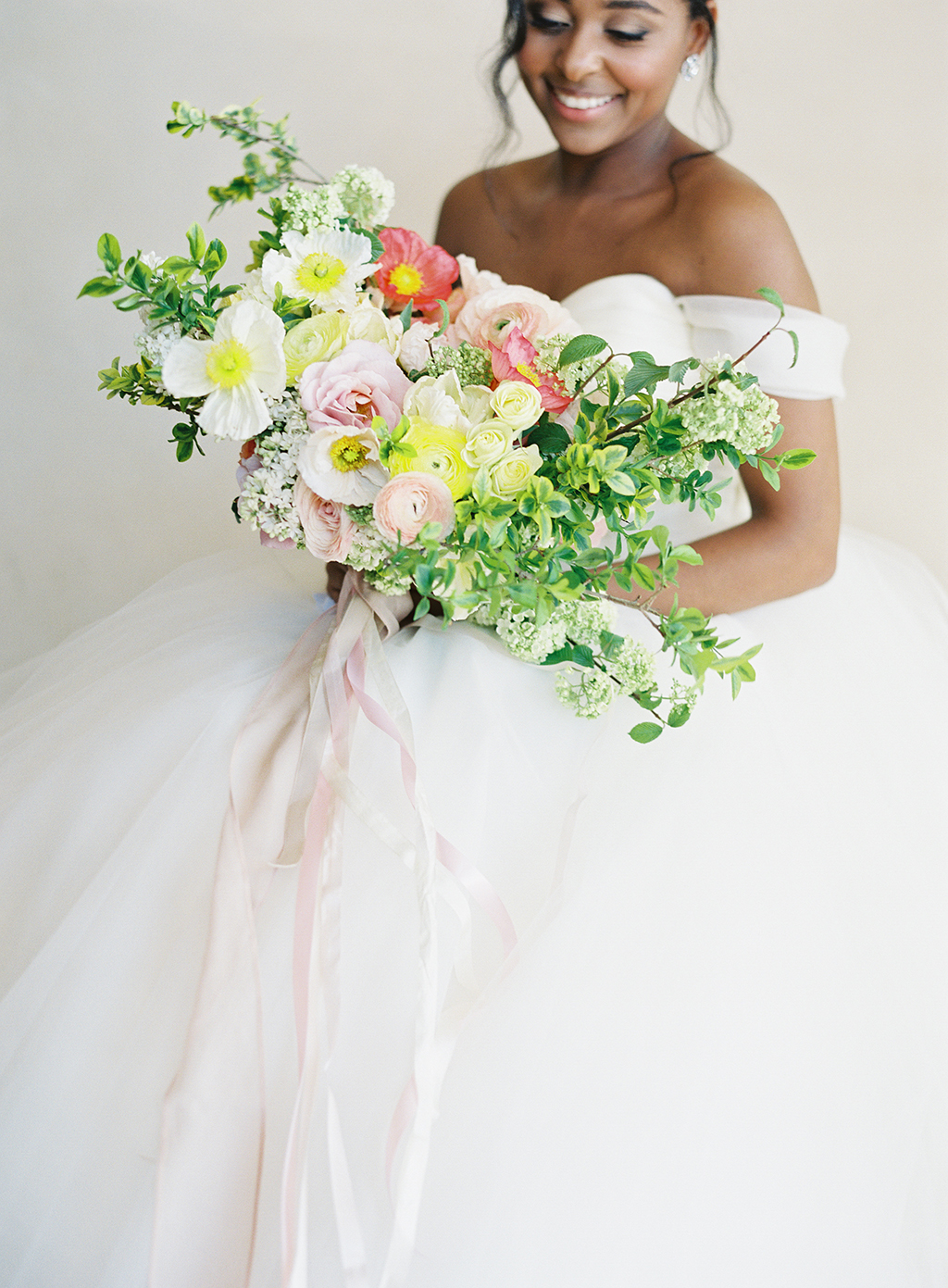 a colorful spring bouquet by art with nature and an amazing wedding gown by lazaro bridal at pelican hill resort