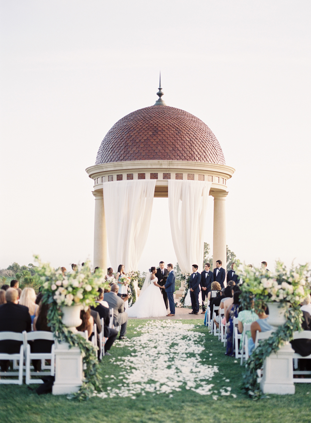 a wedding takes place at pelican hill resort in newport beach, california.