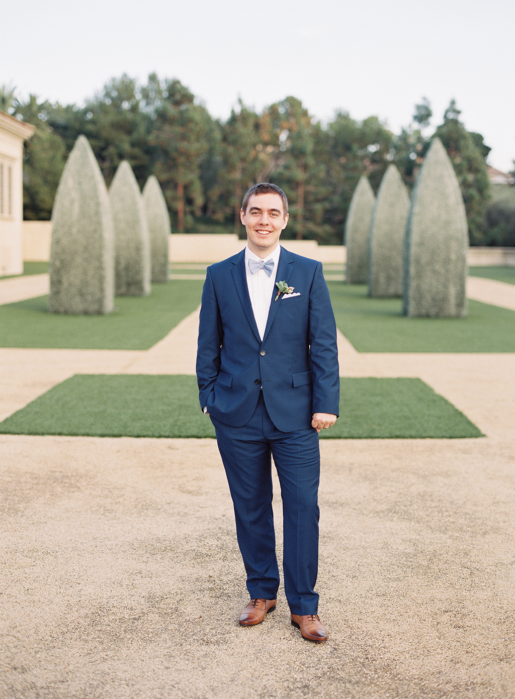 a groom standing for a film photograph at pelican hill resort in newport beach, california