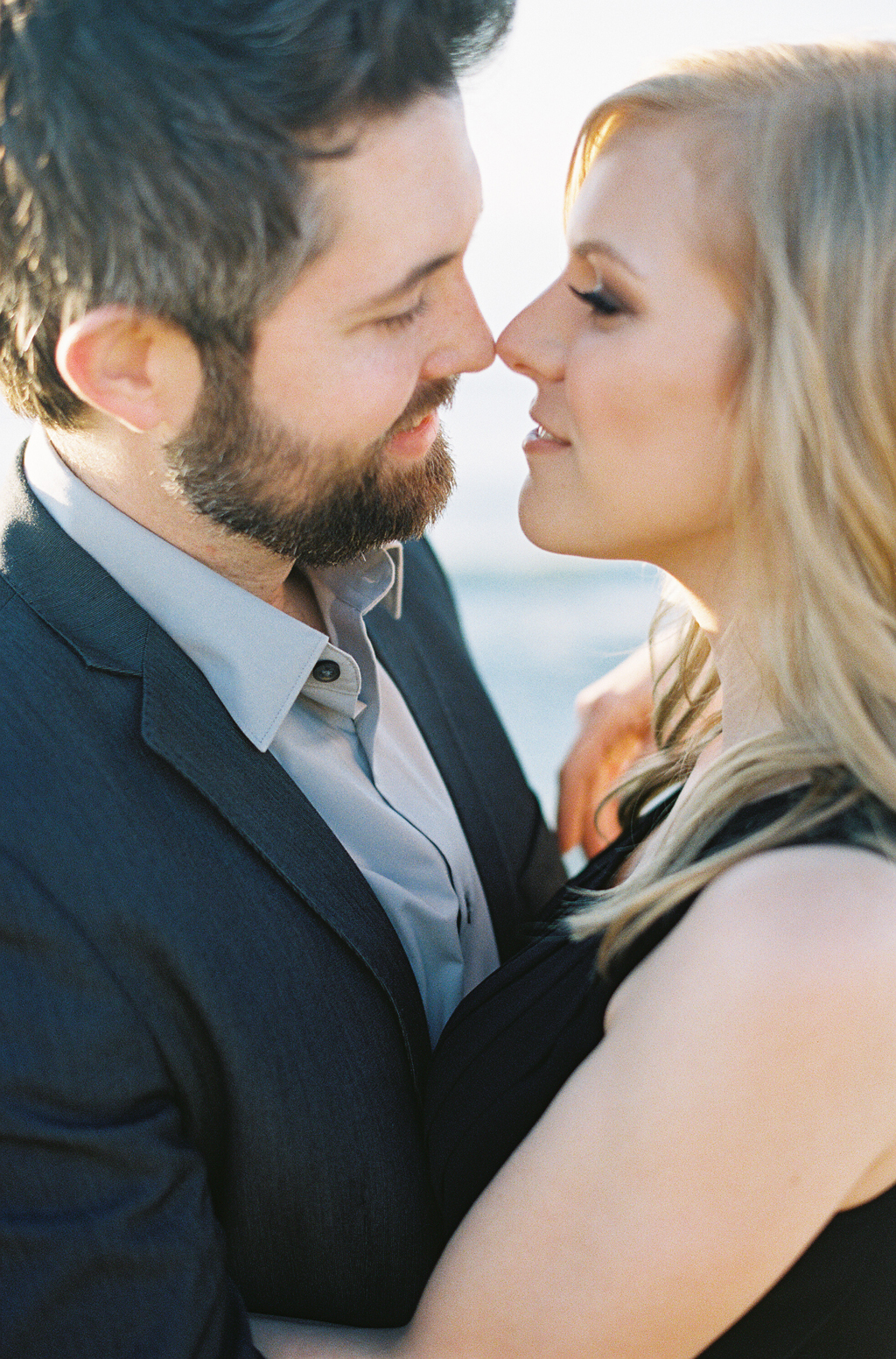 a few months before their wedding, this couple poses for their engagement session along the southern california coast.