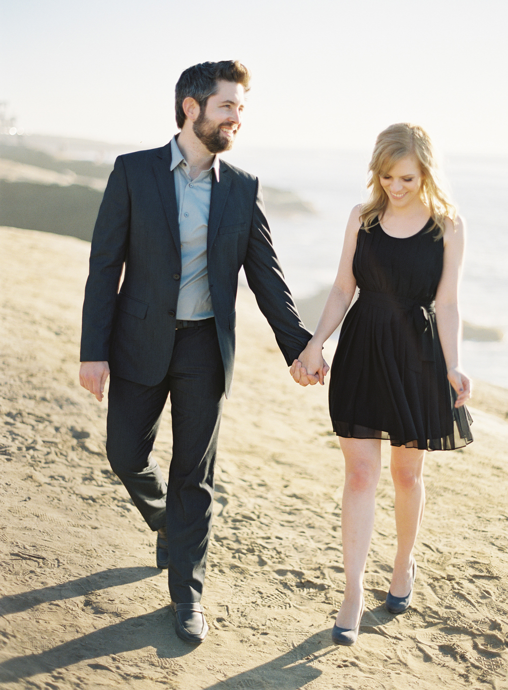 an engaged couple walkes along the coast for their engagement session in southern california with a film photographer.