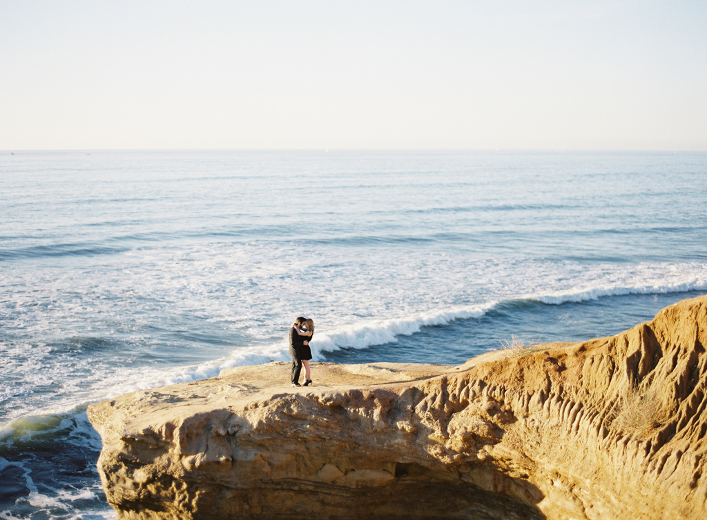 an engaged couple stands on a cliff along the coast for their engagement session.  captured on fuji 400h film and a mamiya 645 camera.