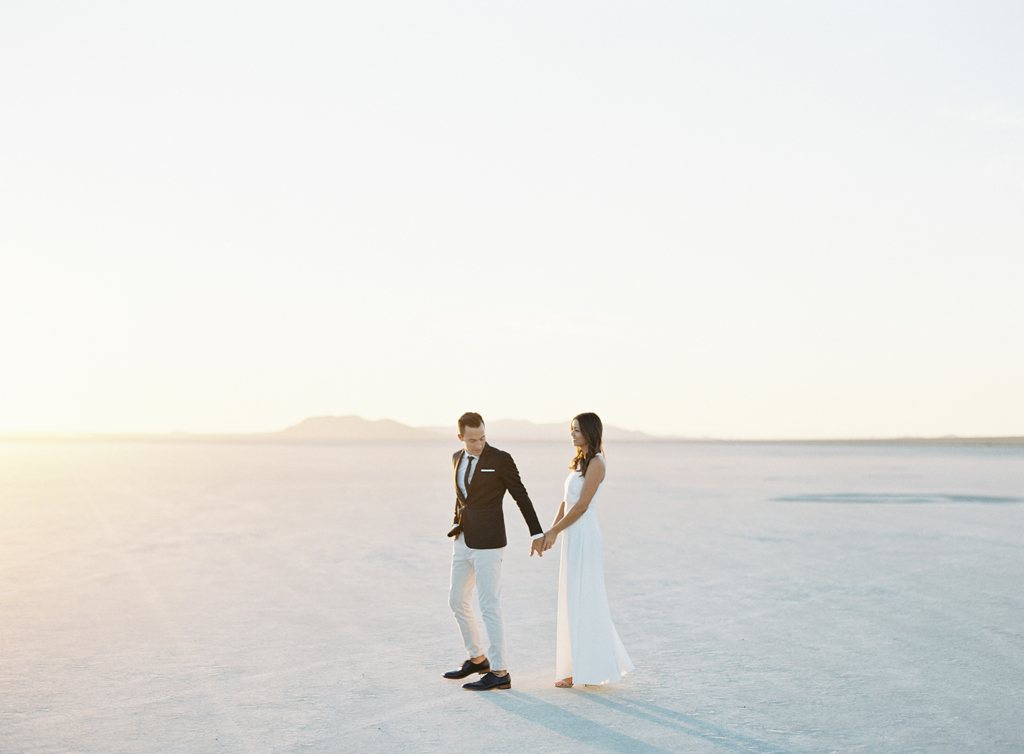 husband and wife walk through the california desert.