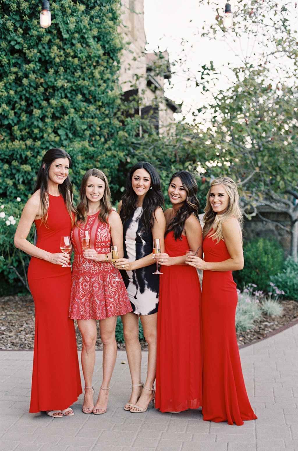 Bridesmaids wearing red dresses during the cocktail hour at a Napa Valley Wedding.