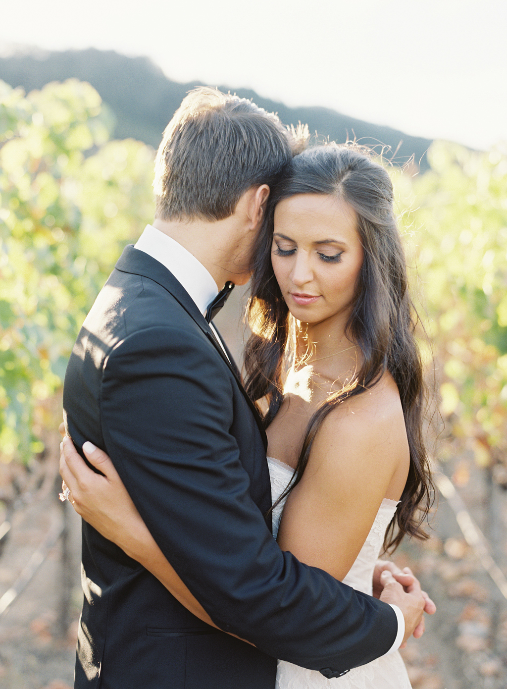 A couple embrace for a portrait in a napa vineyard shot on film photography.