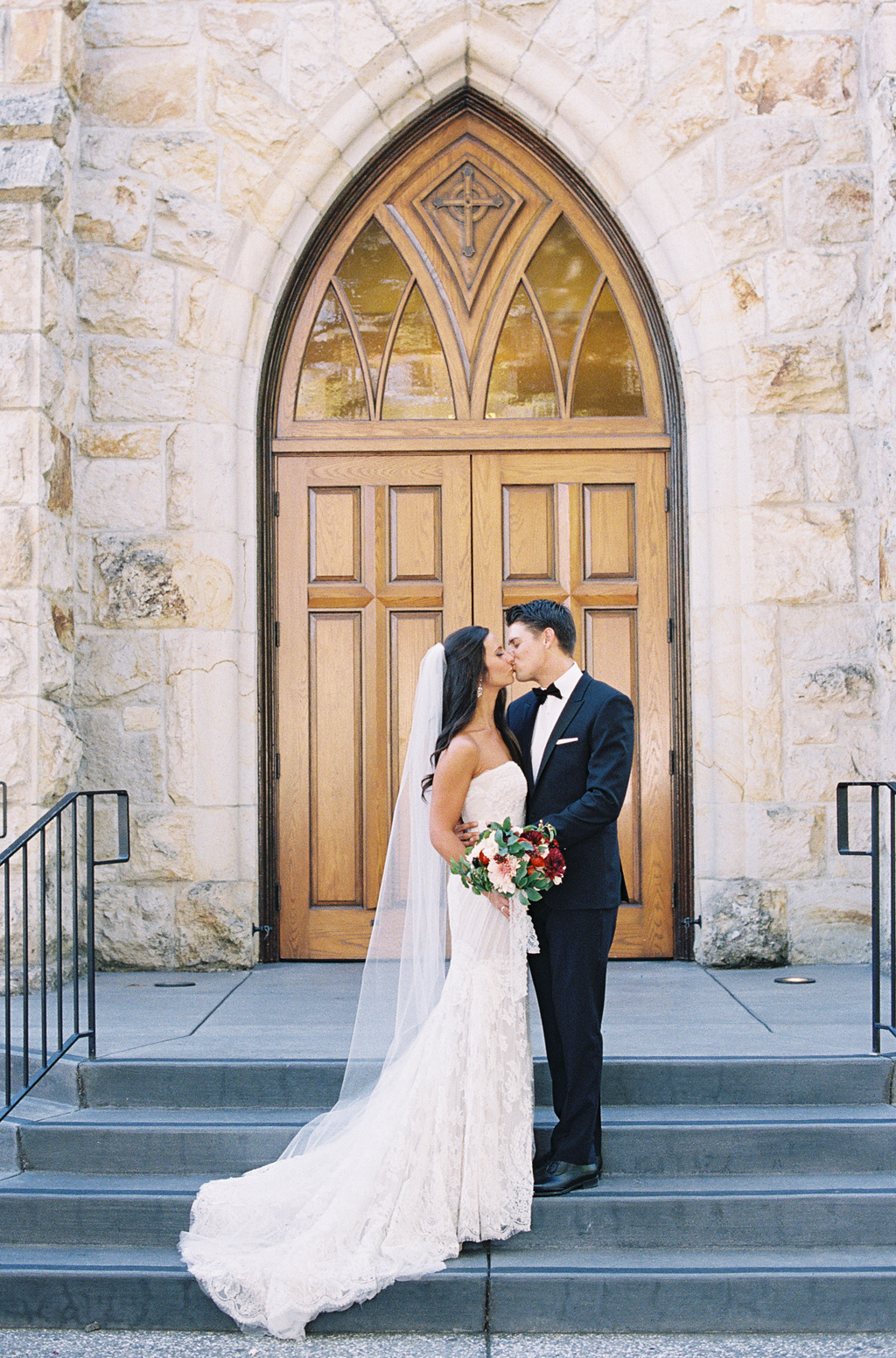 a bride and groom pose in front of a church in St. Helena, California.