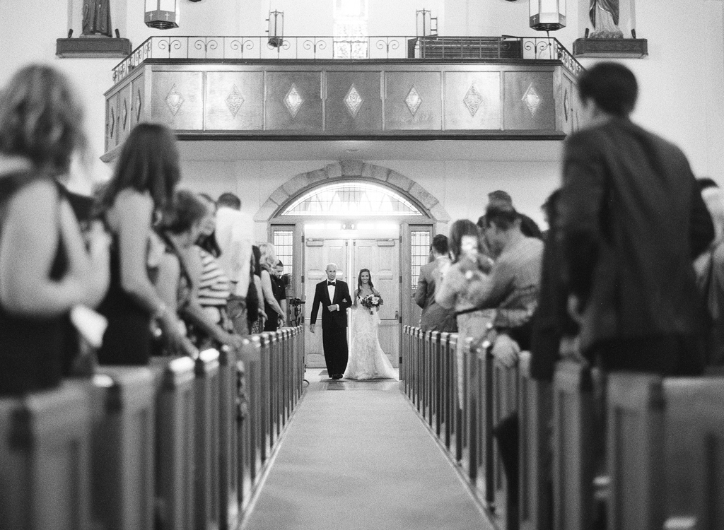 a black and white photo of a bride and her father walking down the aisle during her wedding ceremony.