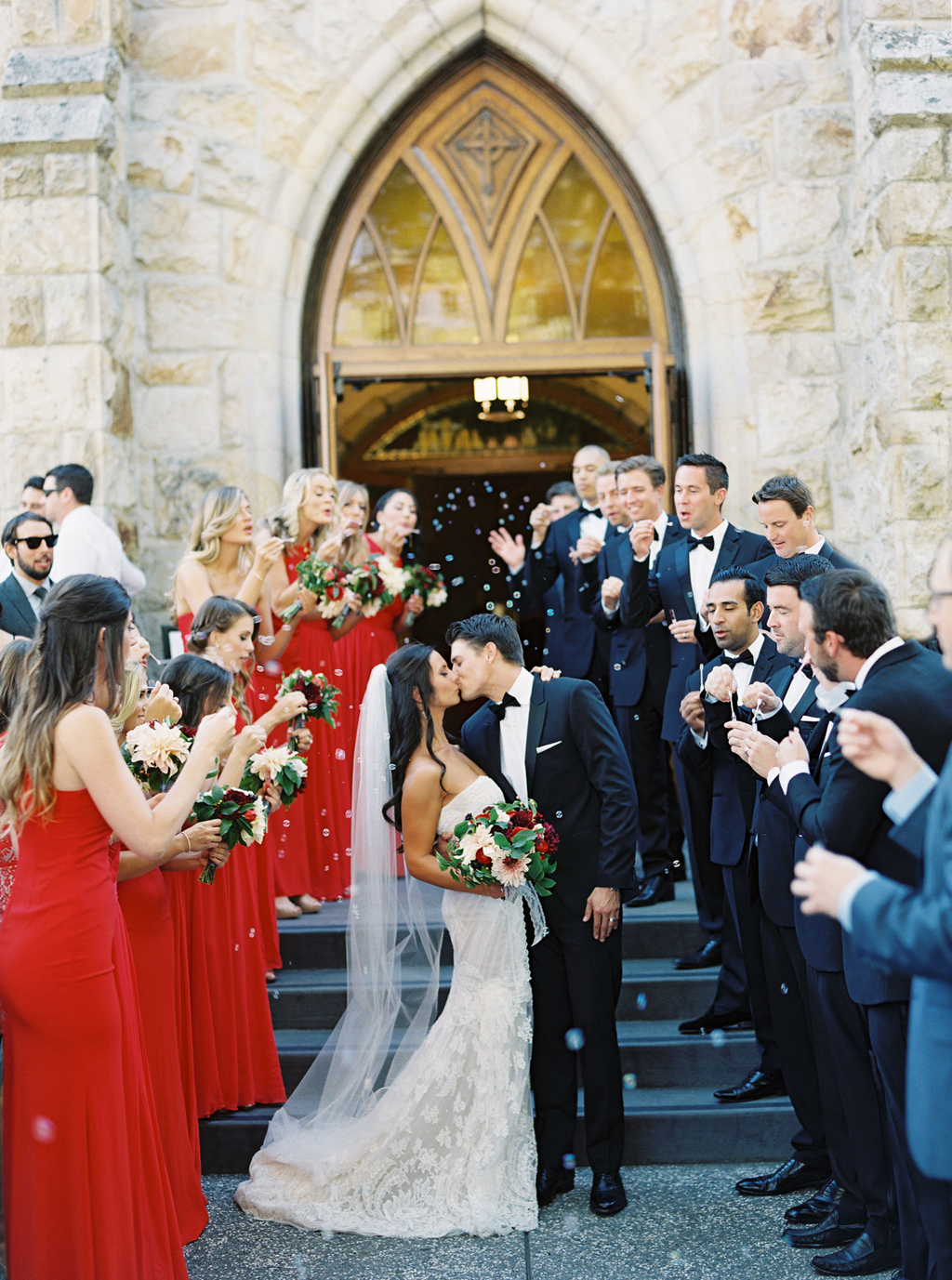 surrounded by their friends, a bride and groom kiss in front of a church in Napa Valley, while bubbles float in the air.