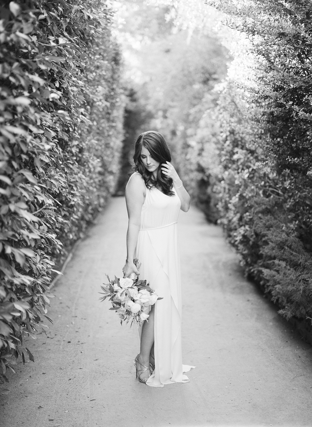 a photo of a bride posing in the pathways at the parker palm springs shot on black and white film.