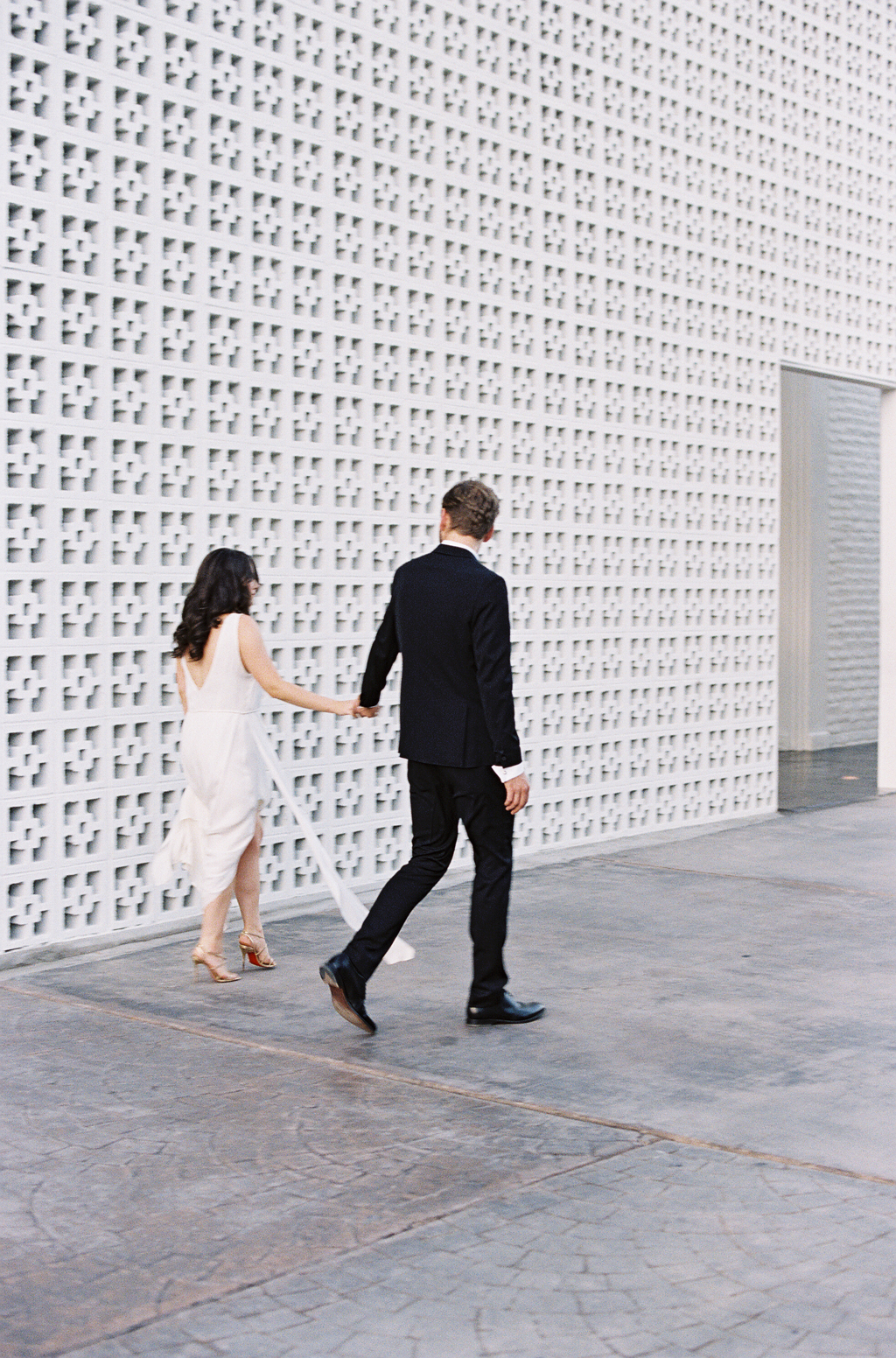 a newly married couple walk near the entrance of the parker palm springs hotel in California.