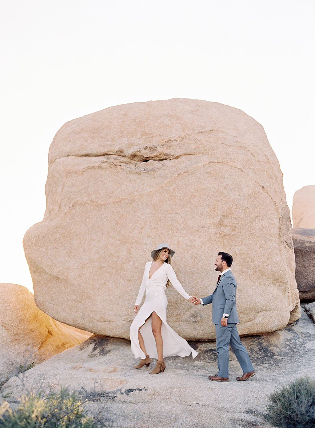 An engaged couple walking through Joshua Tree National Park for their engagement session.